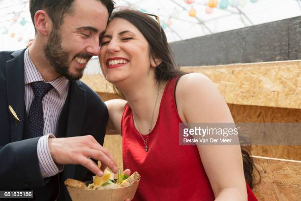 Woman snuggles up to boyfriend, sitting in urban market.