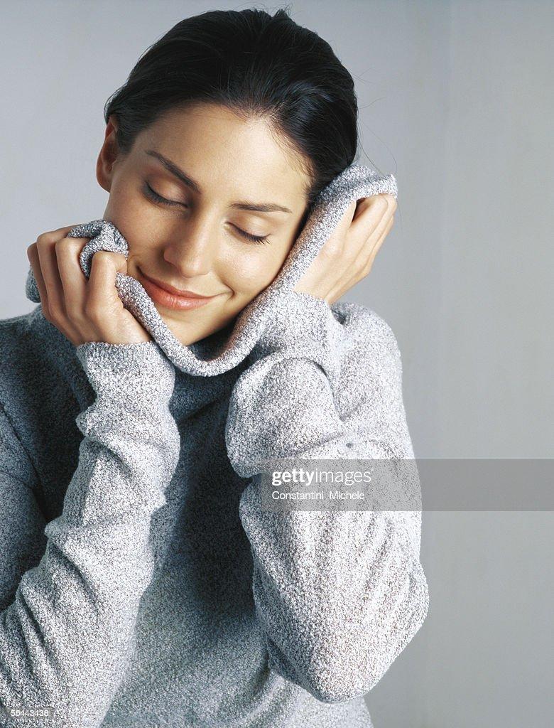 Woman snuggling in sweater, portrait