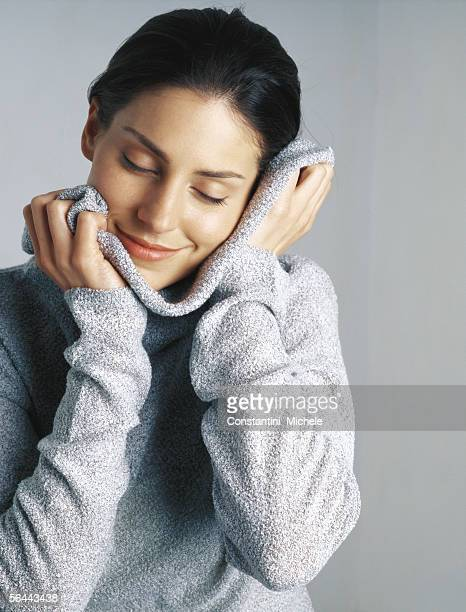 Woman snuggling in sweater, portrait