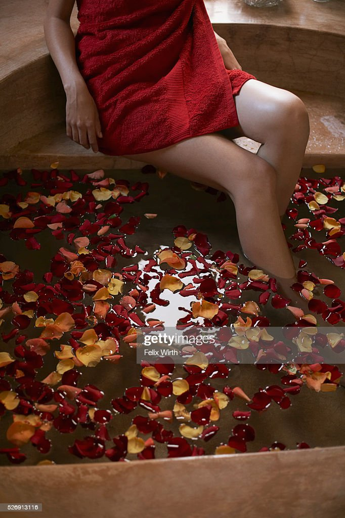 Woman soaking feet in bath with rose petals : Stock Photo