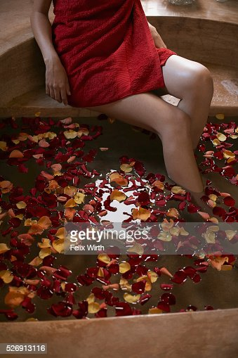 Woman soaking feet in bath with rose petals : Stock-Foto