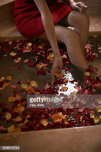 Woman soaking feet in bath with rose petals : Stockfoto