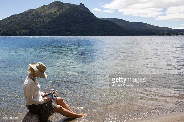 Woman soaking feet in mtn lake while using tablet