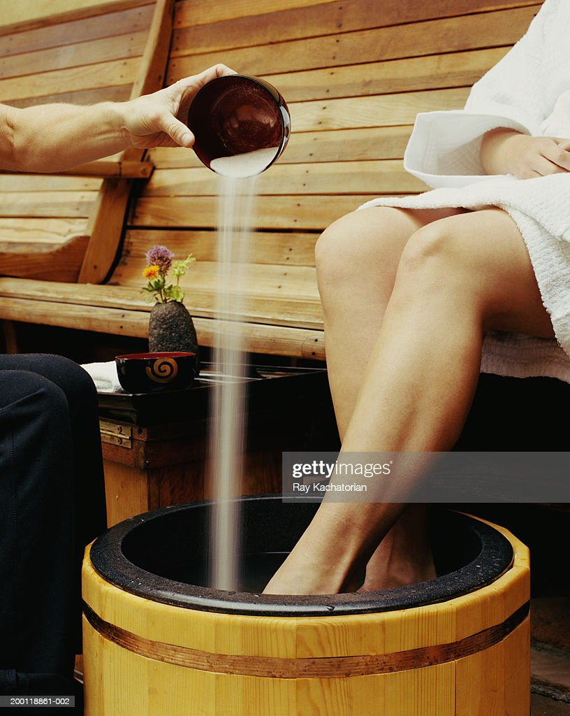 Woman soaking feet in tub, hand pouring sea salt scrub into water : Stock Photo