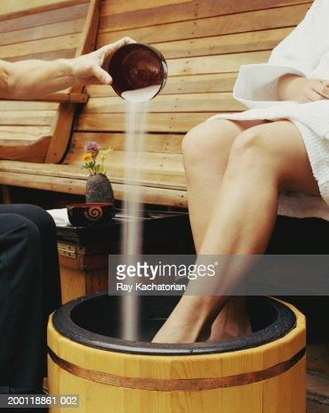 Woman soaking feet in tub, hand pouring sea salt scrub into water : Stock-Foto