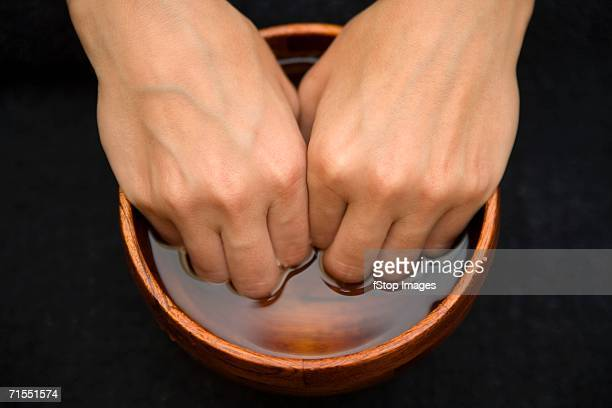 A woman soaking her fingers in a bowl in preparation for a manicure