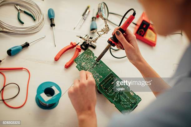 Woman Soldering a circuit board in her office.
