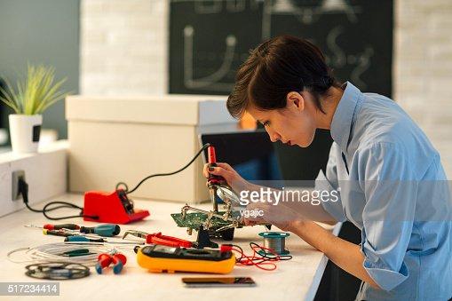 Woman Soldering a circuit board in her tech office.