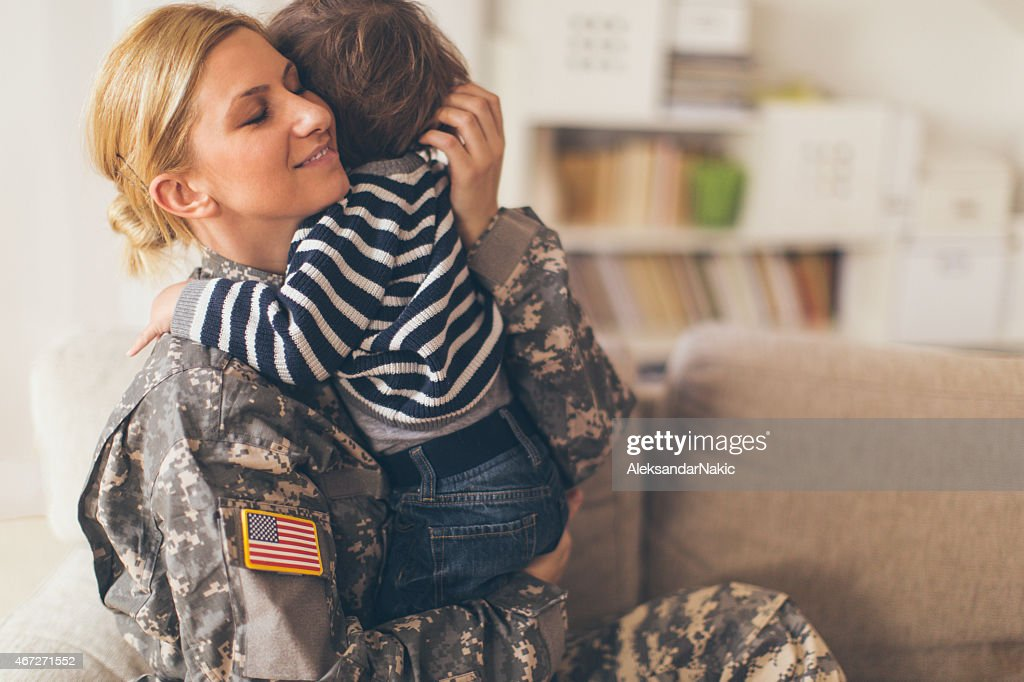 Woman soldier hugging her son : Stock Photo