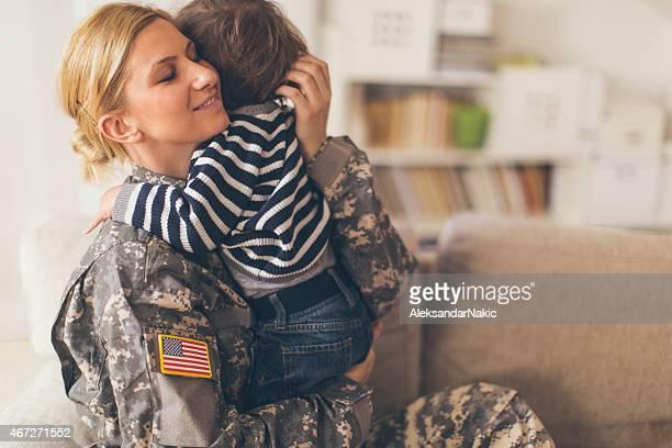 Mujer soldier, que abrazan su hijo