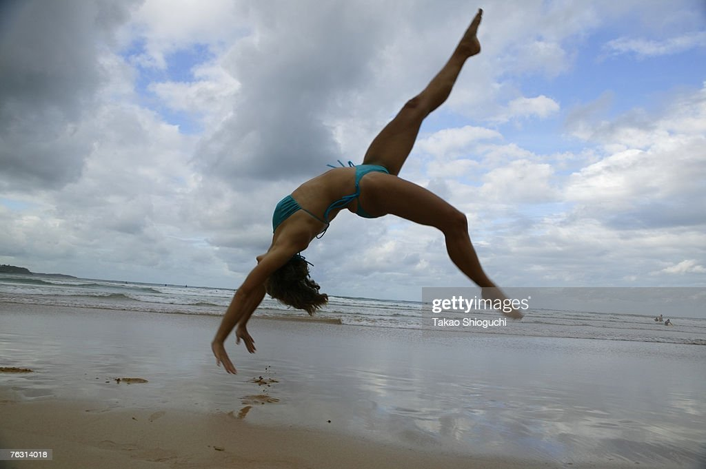Woman somersaulting on beach, side view : Stock Photo