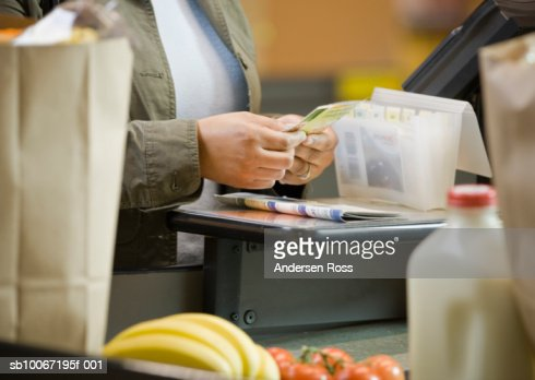 Woman sorting coupons at supermarket, close-up, mid section