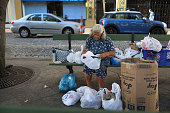 A woman sorts through her belongings on a park bench a day after the speech Puerto Rican Governor Alejandro Garcia Padilla gave regarding the...