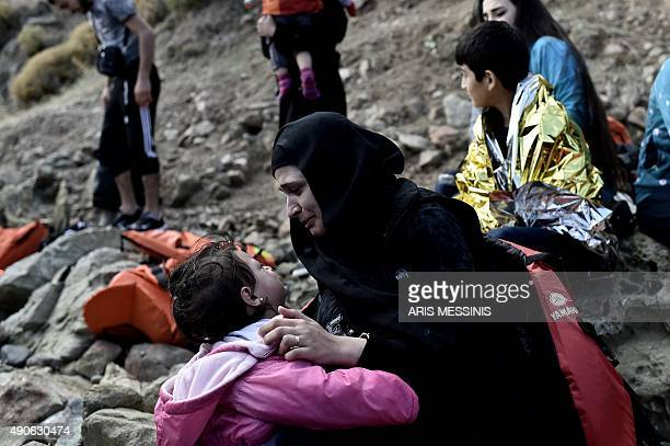A woman speak with her child as refugees and migrants arrive on the Greek island of Lesbos after crossing the Aegean sea from Turkey on September 30...