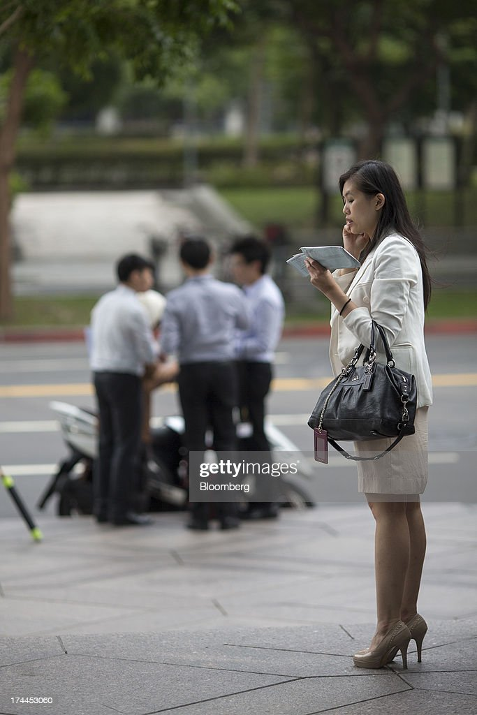 A woman speaks on a mobile phone outside the Taipei 101 building in Taipei, Taiwan, on Wednesday, July 24, 2013. Taiwan President Ma Ying-jeou ruled out driving down the Taiwan dollar to boost exports following the currencys rally against the yen and said the government still aims for growth of at least 2 percent this year. Photographer: Jerome Favre/Bloomberg via Getty Images