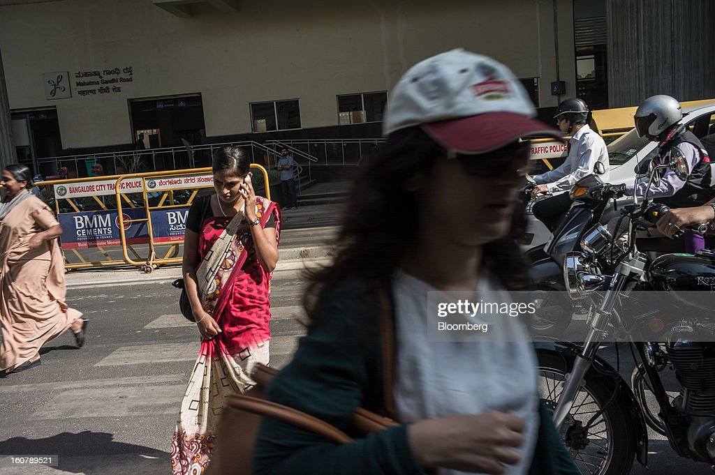 A woman speaks on a mobile phone while crossing the road outside the Bangalore Metro Rail Corp. (BMRCL) Mahatma Gandhi Road station in Bangalore, India, on Tuesday, Feb. 5, 2013. India's monetary authority predicted that the economy will expand 5.5 percent in the year ending March 31, which would be the smallest gain since 2003. Photographer: Sanjit Das/Bloomberg via Getty Images