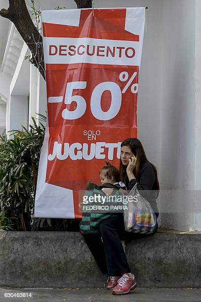 A woman speaks on her mobile phone next to a banner announcing discounts on toys for the Christmas season in Caracas on December 22 2016 / AFP /...