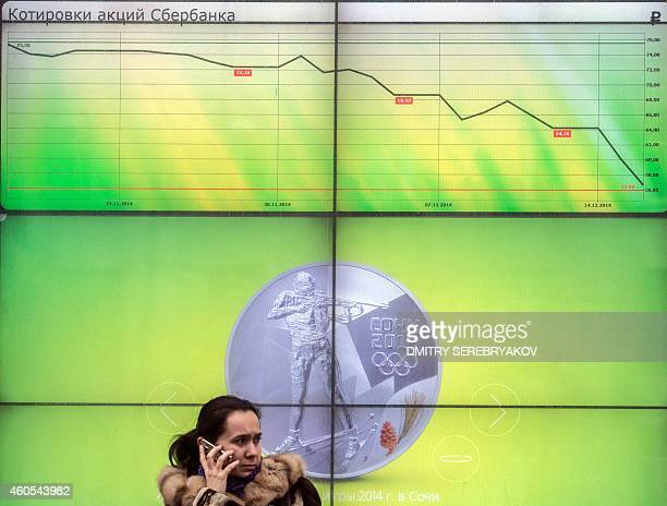 A woman speaks on her mobile phone next to a screen displaying Sberbank's the largest stateowned bank in Russia shares quotation in Moscow on...