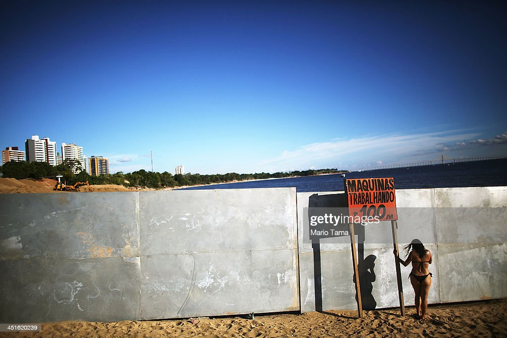A woman speaks on her phone at Ponta Negra beach on Rio Negro a branch of the Amazon River on November 23 2013 in Manaus Brazil Manaus' Arena...