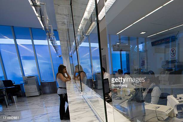 A woman speaks with a teller at a Grupo Financiero Inbursa SAB bank branch in Mexico City Mexico on Tuesday June 25 2013 CaixaBank SA raised 125...