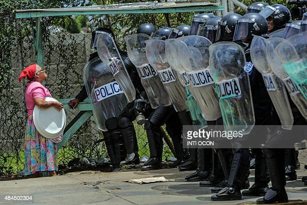 A woman speaks with riot policemen asking permission to go the her house during a protest against the electoral system in Managua on August 19 2015...