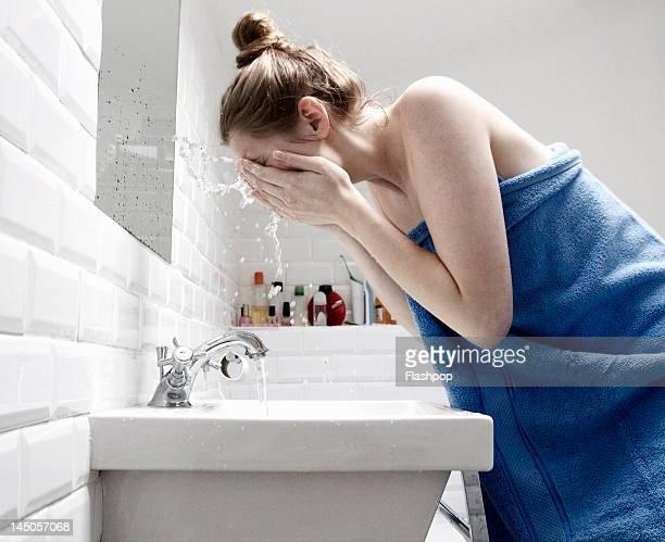 Woman splashing face with water