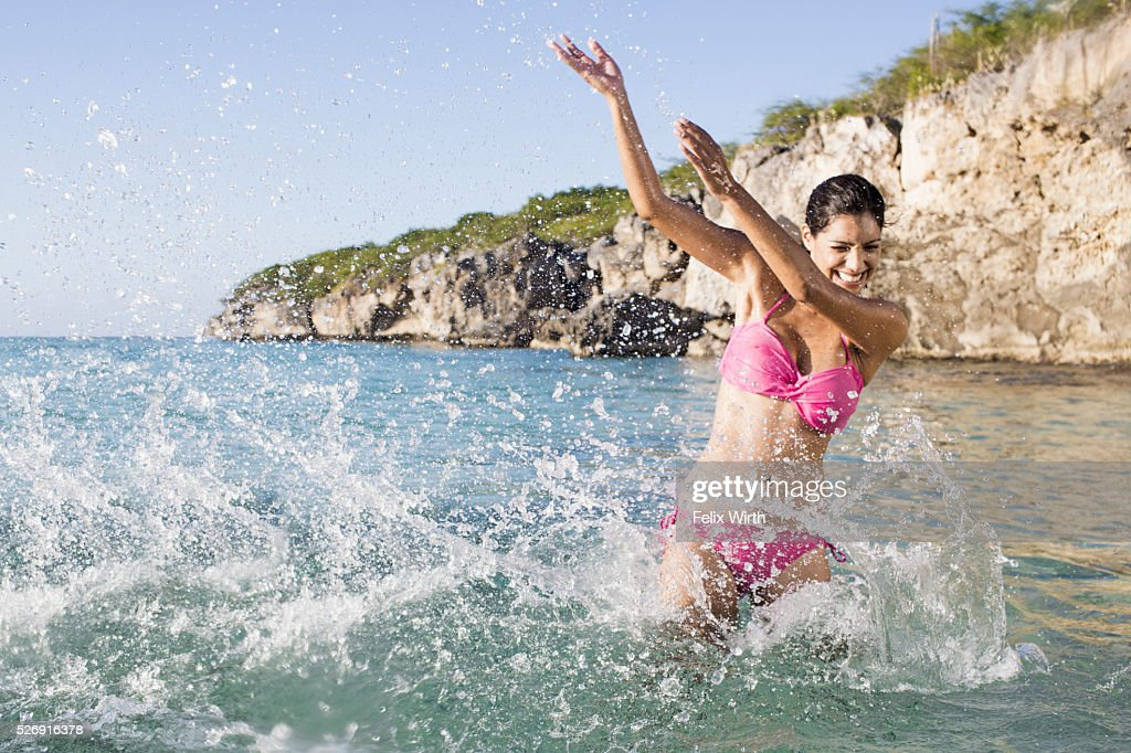 Woman splashing in sea : Stockfoto