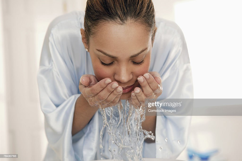 Woman splashing water on face : Stock Photo