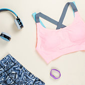 Woman sport bra, leggins, sneakers and fitness tracker on neutral background. Sport fashion concept. Flat lay, top view