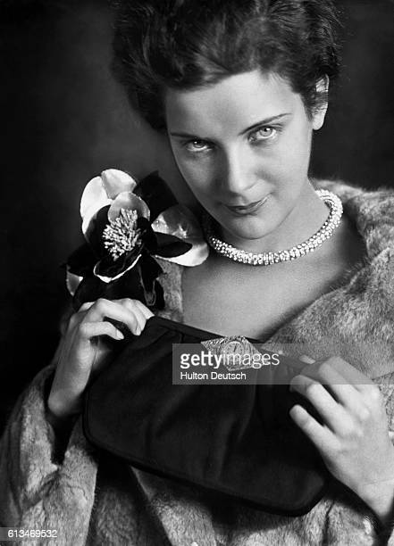 A woman sporting a fur coat and corsage holds a clutch bag bearing a small clock face