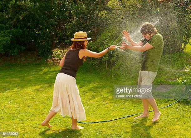 Woman spraying man with garden hose