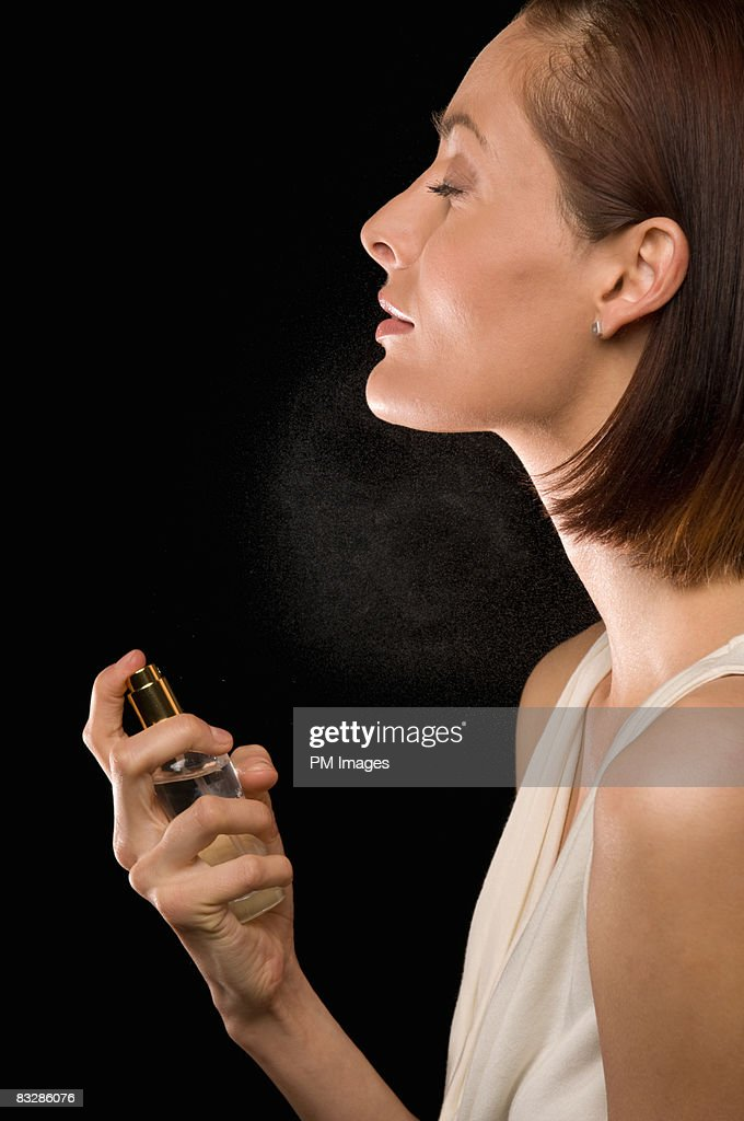 Woman spraying neck with perfurme : Stock Photo