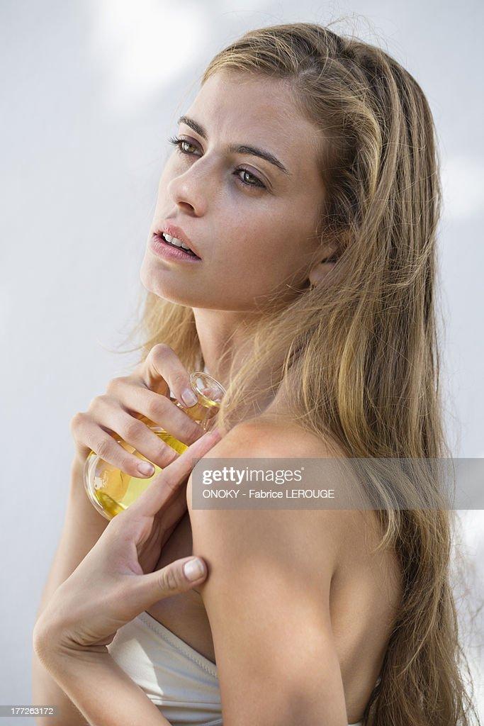 Woman spraying perfume on her body