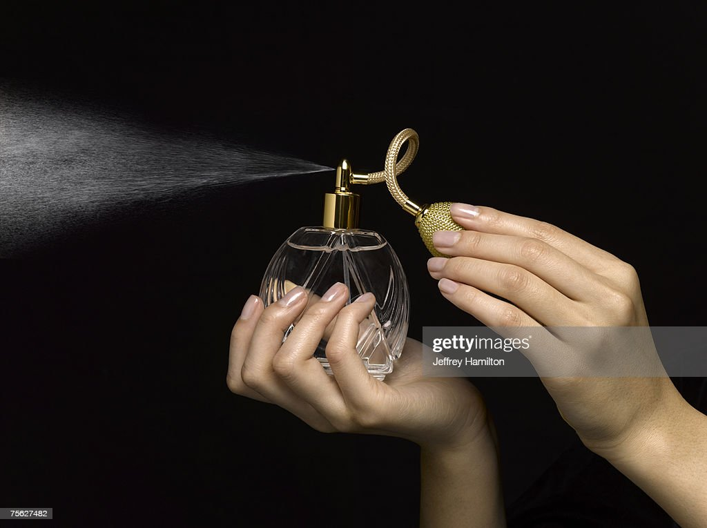 Woman spraying perfume with perfume atomizer, close-up of hands : Stock Photo