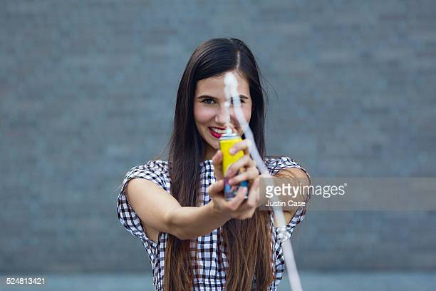 woman spraying spray string towards the camera
