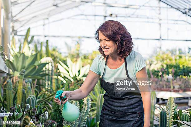 Woman spraying water on plants at garden center