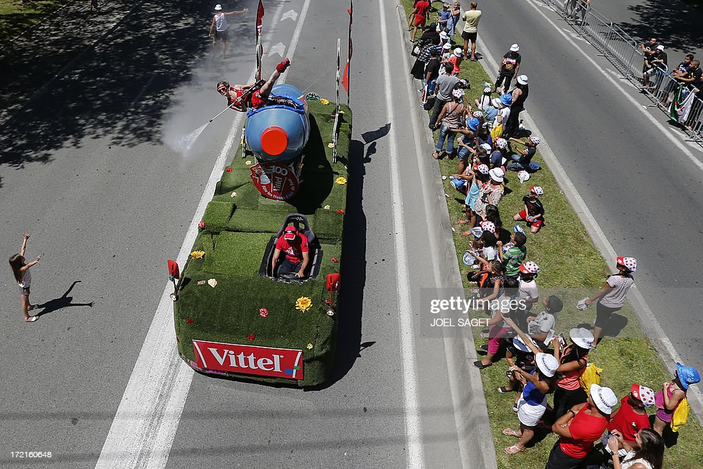 A woman sprays water on spectators from a Vittel vehicle belonging to the Tour de France advertising caravan before the start of the 25 km team time-trial and fourth stage of the 100th edition of the Tour de France cycling race on July 2, 2013 around Nice, southeastern France.