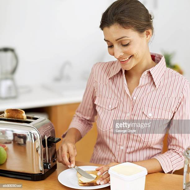 woman spreading butter on toast