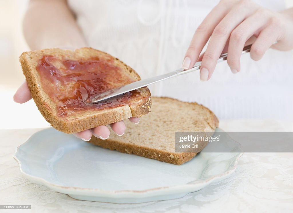 Woman spreading jam on bread, close-up, mid section
