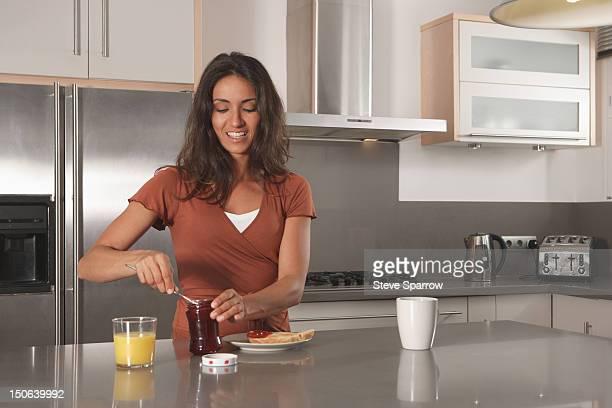 Woman spreading jam on toast in kitchen