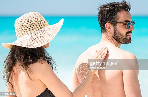 woman spreading the sun protection on the man skin