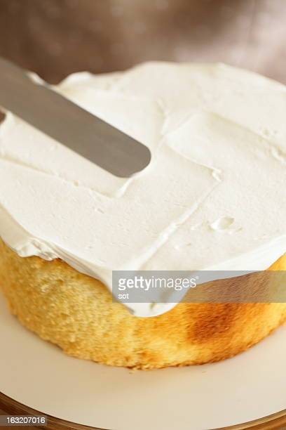 Woman spreading whipped cream on sponge cake