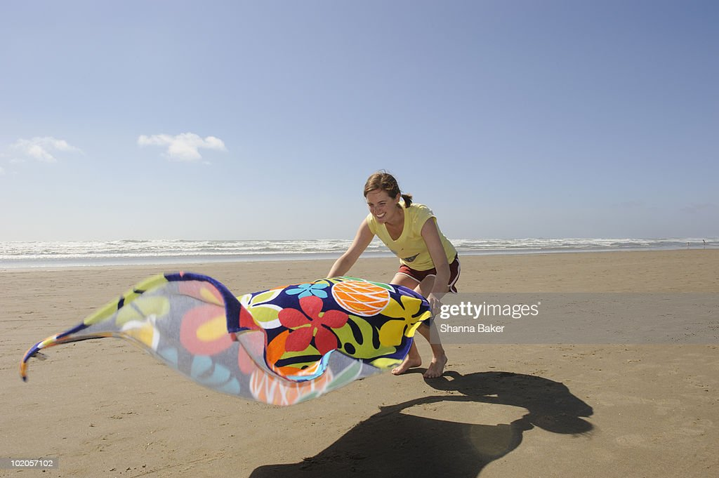 A woman spreads out a towel on the beach