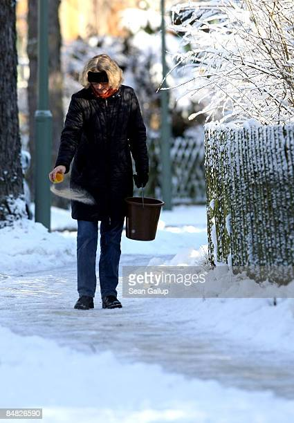 A woman spreads sand along at a frozen sidewalk in front of her home in Zehlendorf district on February 17 2009 in Berlin Germany Germany has been...