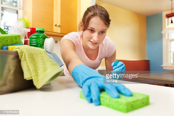 Woman Spring Cleaning Kitchen Counter with Cleanser and Sponge