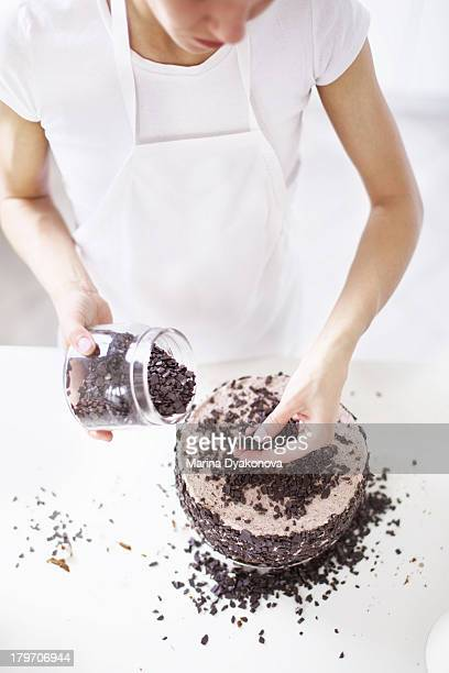 Woman sprinkling chocolate chips on cake