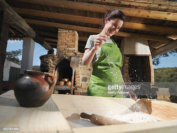 Woman sprinkling salt in bread dough