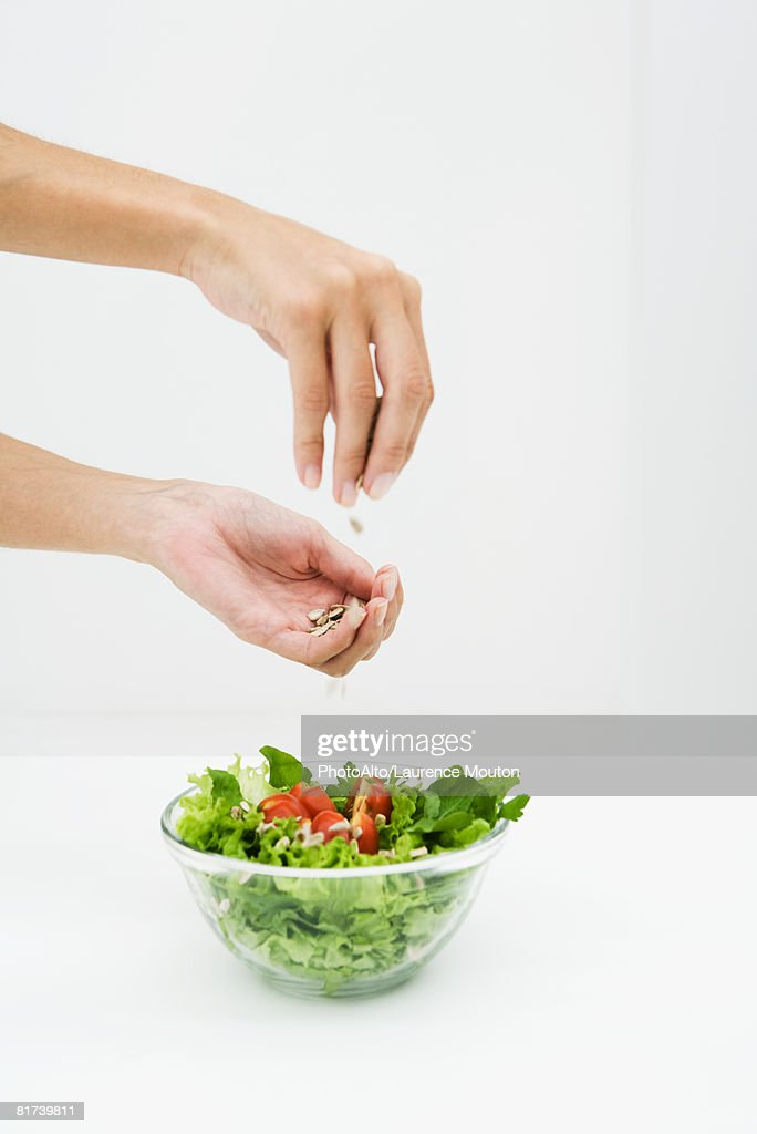 Woman sprinkling sunflower seeds on salad, cropped view of hands : Stock Photo