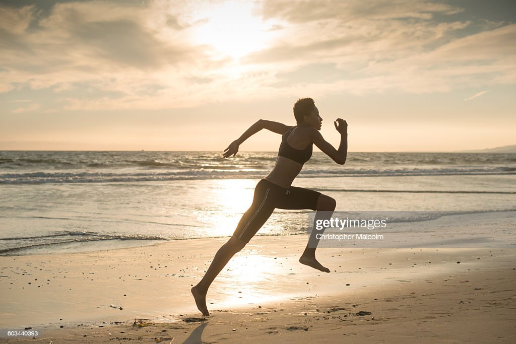 Woman sprints on the beach