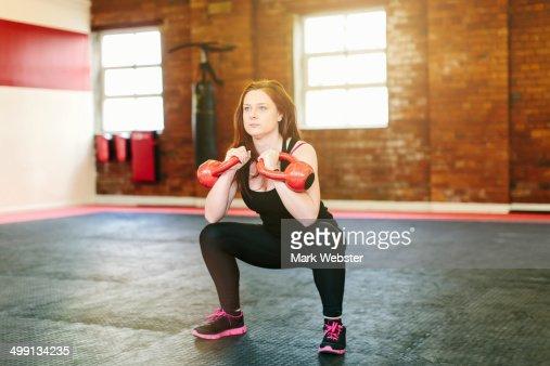 Woman squatting lifting kettlebells